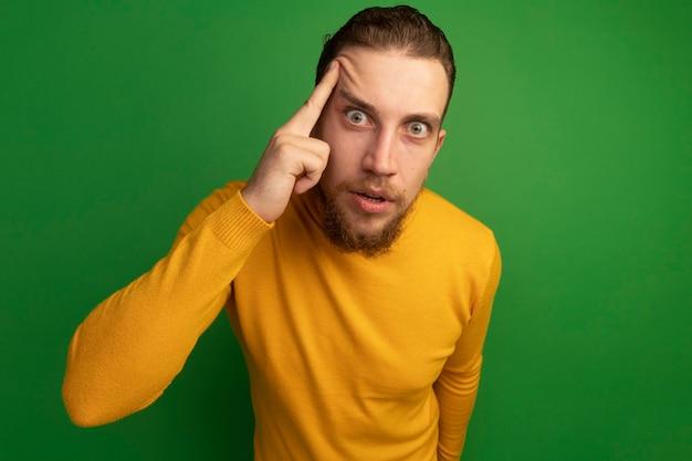 놀란 잘 생긴 금발의 남자는 사원에 손가락을 넣고 녹색에 카메라를 찾습니다
