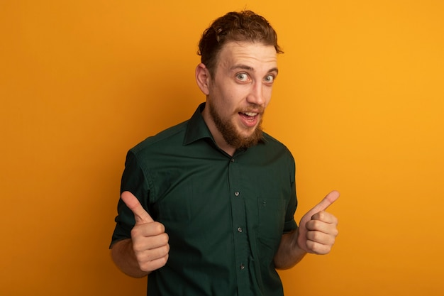 Удивленный красивый белокурый мужчина показывает палец вверх двух рук, изолированных на оранжевой стене