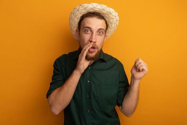 Uomo biondo bello sorpreso con cappello da spiaggia tiene la mano vicino alla bocca e punti dietro isolato sulla parete arancione