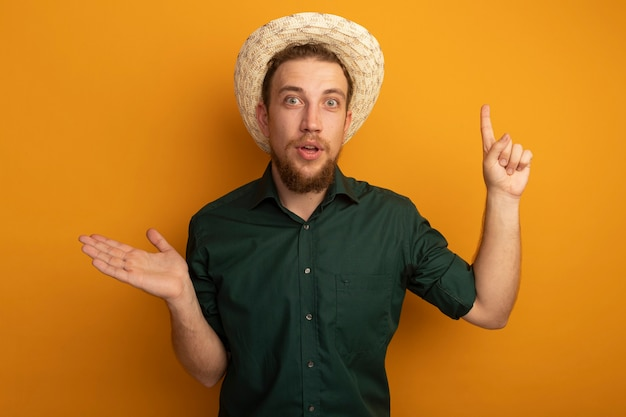 ビーチ帽子をかぶった驚いたハンサムなブロンドの男は手を開いて、オレンジ色の壁に孤立して上向きを指します