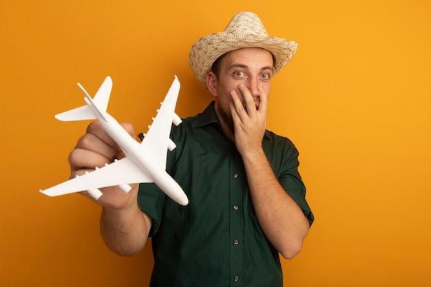 Uomo biondo bello sorpreso con cappello da spiaggia mette la mano sul viso e tiene l'aereo modello isolato sulla parete arancione