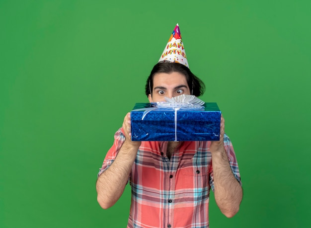 Surprised handsome caucasian man wearing birthday cap holding and looking at gift box
