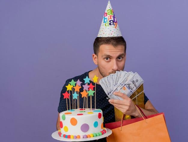 Uomo caucasico bello sorpreso che indossa il cappello di compleanno tiene il contenitore di regalo del sacchetto di shoppig della carta della torta di birhtday e soldi isolati su fondo viola con lo spazio della copia