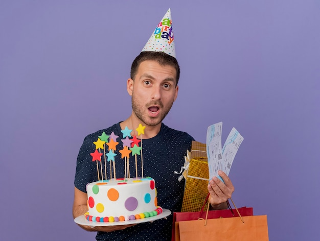 Surprised handsome caucasian man wearing birthday cap holds birthday cake paper shopping bag gift box and air tickets isolated on purple background with copy space