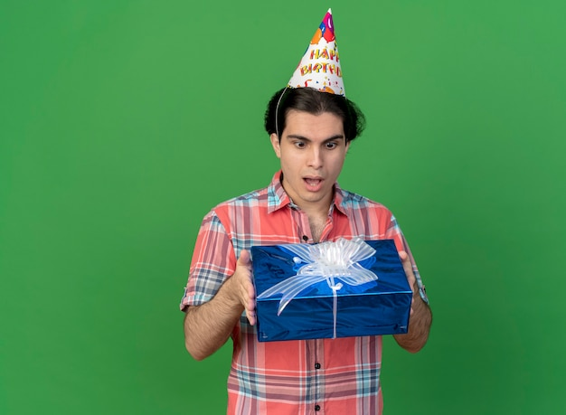 Surprised handsome caucasian man wearing birthday cap holds and looks at gift box