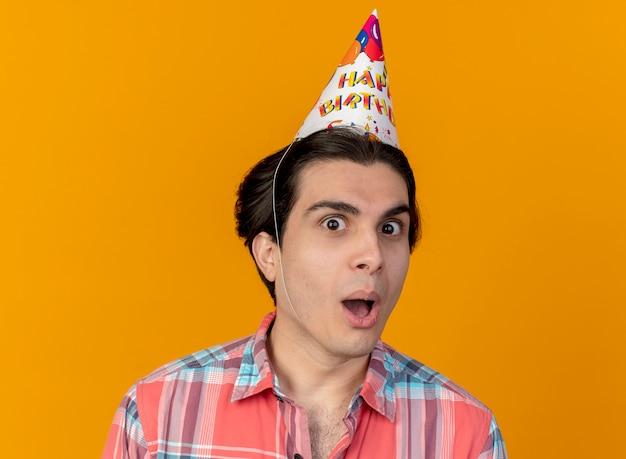 Surprised handsome caucasian man wearing birthday cap looks at camera