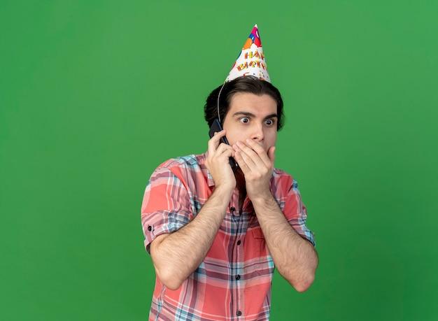 생일 모자를 쓰고 놀란 잘 생긴 백인 남자가 전화로 이야기하는 입에 손을 넣습니다.