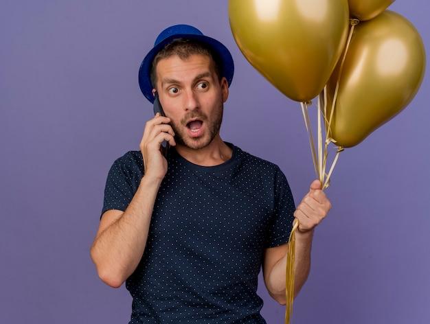 L'uomo caucasico bello sorpreso che porta il cappello blu tiene gli aerostati dell'elio che parlano sul telefono isolato su fondo viola con lo spazio della copia