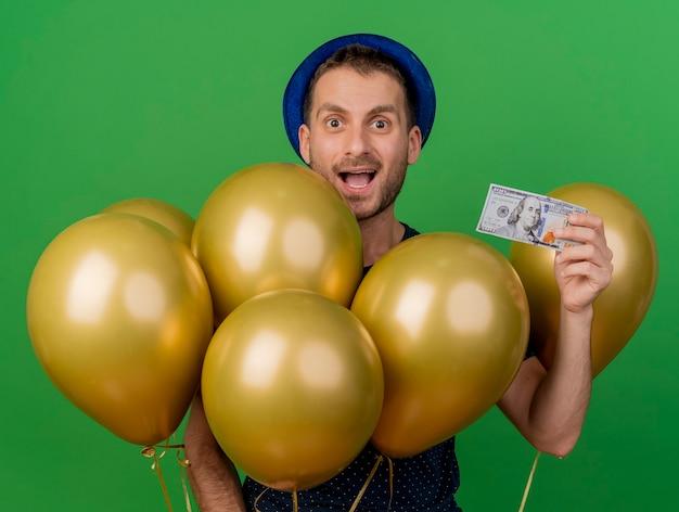 블루 파티 모자를 쓰고 놀된 잘 생긴 백인 남자는 헬륨 풍선과 복사 공간이 녹색 배경에 고립 된 돈을 보유