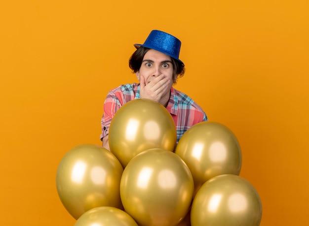 L'uomo caucasico bello sorpreso che porta il cappello blu del partito mette la mano sulla bocca e si leva in piedi