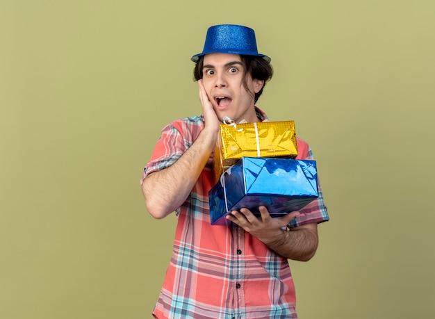 파란색 파티 모자를 쓰고 놀란 잘 생긴 백인 남자가 얼굴에 손을 넣고 선물 상자를 보유하고 있습니다.