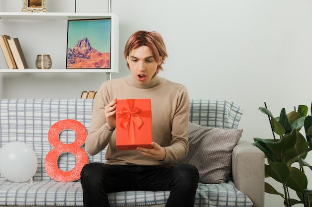 Удивленный красивый парень в счастливый женский день, держащий и смотрящий на настоящее, сидя на диване в гостиной