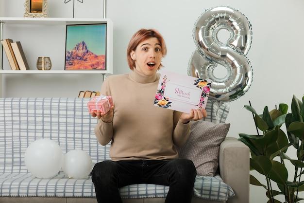 リビングルームのソファに座っているグリーティングカードとプレゼントを保持している幸せな女性の日に驚いたハンサムな男
