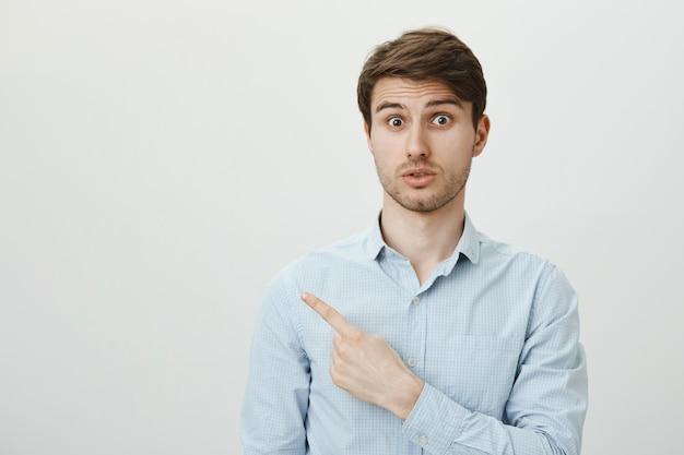 Surprised handsome guy pointing finger upper left corner at advertisement