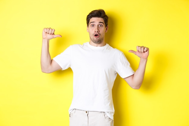 Surprised handsome guy pointing at himself, looking amazed, standing over yellow background