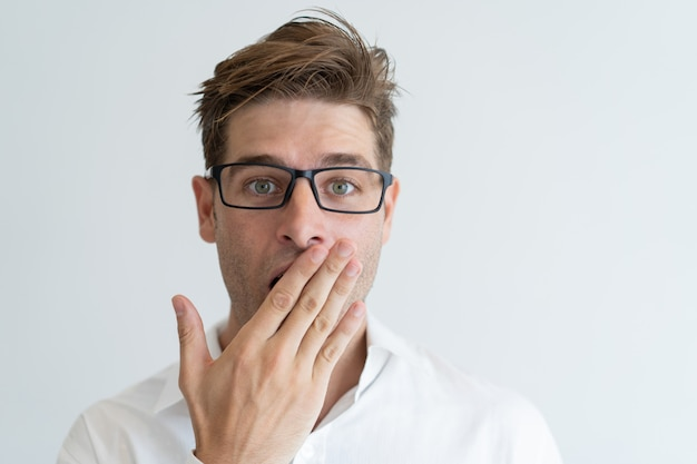 Surprised handsome man covering mouth with hand