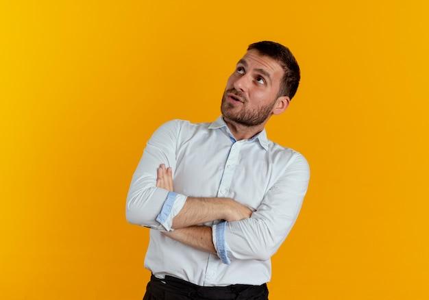L'uomo bello sorpreso attraversa le braccia alzando lo sguardo isolato sulla parete arancione
