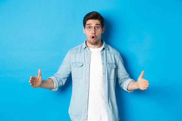 青い背景の上に立って、驚いた顔で大きなサイズを示して、何か大きなものを持っている驚いたハンサムな男。