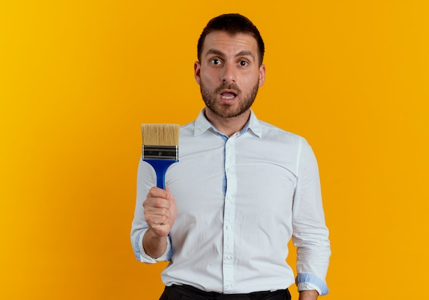 驚いたハンサムな男はオレンジ色の壁に分離されたブラシを保持します