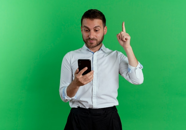 Surprised handsome man holds and looks at phone pointing up isolated on green wall