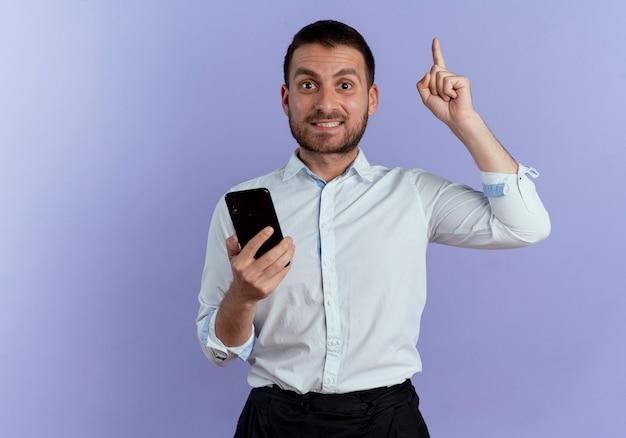 L'uomo bello sorpreso tiene il telefono e indica in alto isolato sulla parete viola
