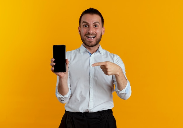 Surprised handsome man holds and points at phone isolated on orange wall