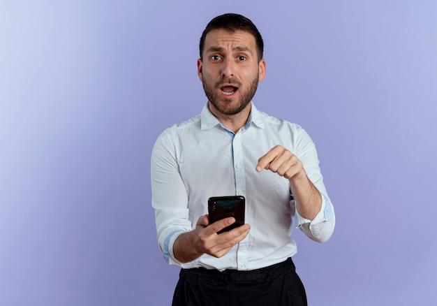 L'uomo bello sorpreso tiene e indica il telefono isolato sulla parete viola