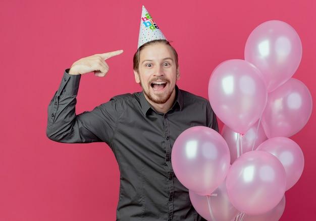 생일 모자에 놀란 잘 생긴 남자는 모자를 가리키는 헬륨 풍선으로 서