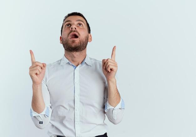 L'uomo bello sorpreso guarda e indica con due mani isolate sulla parete bianca