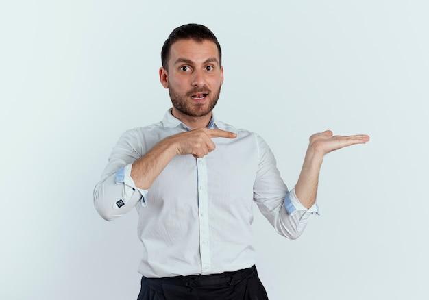 L'uomo bello sorpreso indica la mano vuota isolata sulla parete bianca