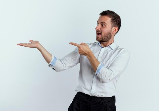 L'uomo bello sorpreso indica ed esamina la mano vuota isolata sulla parete bianca