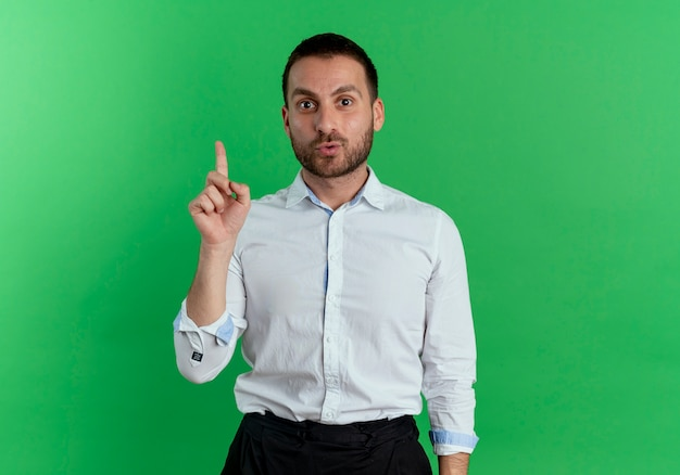 Surprised handsome man points up looking isolated on green wall