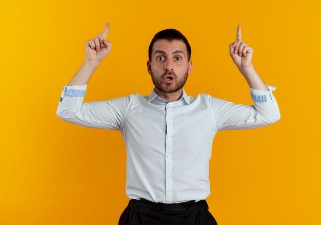 놀란 된 잘 생긴 남자는 오렌지 벽에 고립 된 찾고 두 손으로 포인트