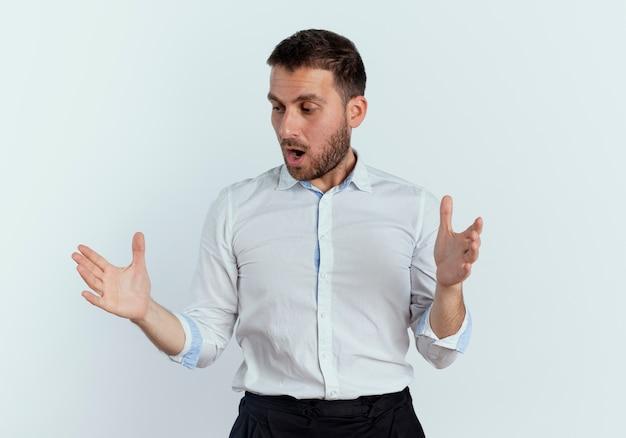 놀란 잘 생긴 남자가 뭔가를 잡고있는 척하고 흰 벽에 고립 된 손에 보이는
