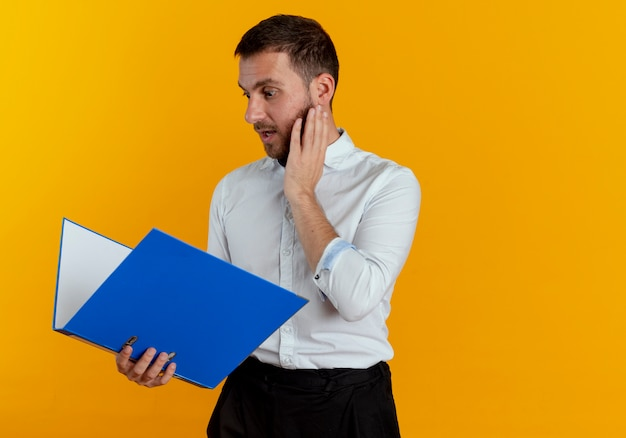 Surprised handsome man puts hand on face holding and looking at file folder isolated on orange wall