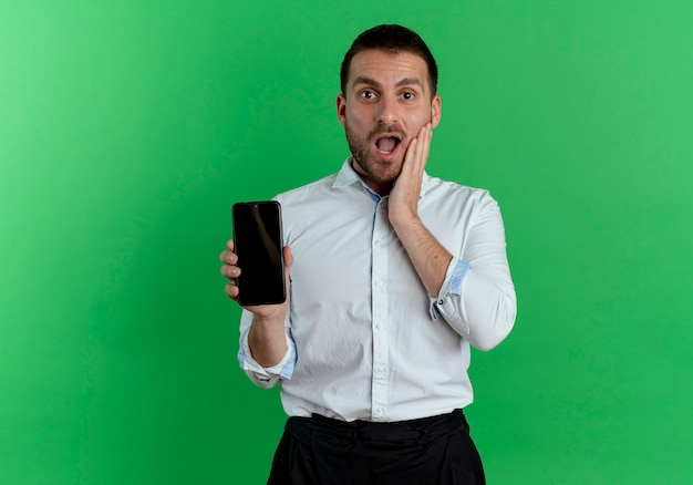 Surprised handsome man puts hand on face and holds phone isolated on green wall
