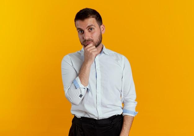 驚いたハンサムな男はオレンジ色の壁に隔離されたあごに手を置きます