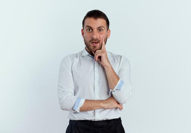 驚いたハンサムな男は白い壁に孤立して見えるあごに手を置きます