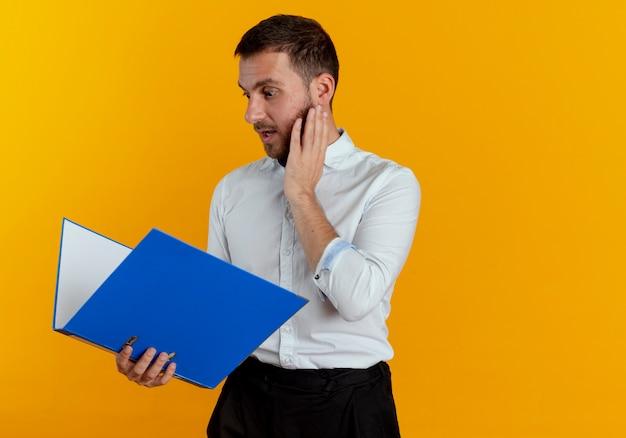 Удивленный красавец кладет руку на лицо, держа и глядя на папку с файлами, изолированную на оранжевой стене