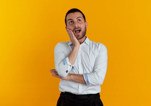 Удивленный красавец кладет руку на лицо, глядя вверх изолированно на оранжевой стене