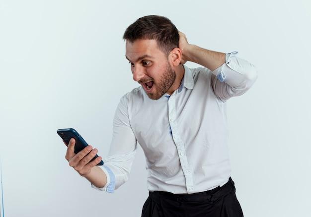 驚いたハンサムな男は白い壁に隔離された電話を見て後ろの頭に手を置きます