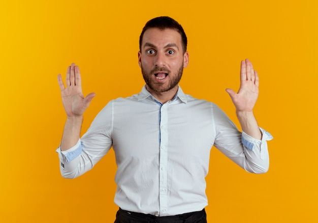 오렌지 벽에 고립 된 두 손을 올리는 놀된 잘 생긴 남자