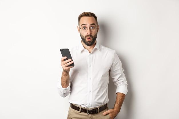 Удивленный красавец, читающий интересную информацию в интернете, держа смартфон, стоя.