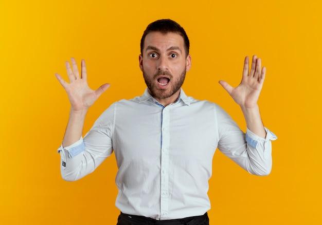 놀란 된 잘 생긴 남자는 오렌지 벽에 고립 된 두 손을 올리는 스탠드