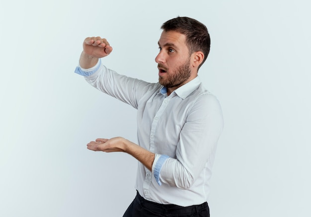 Bell'uomo sorpreso si leva in piedi lateralmente fingendo di tenere qualcosa di isolato sul muro bianco