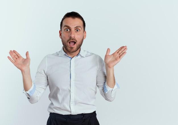 L'uomo bello sorpreso sta con le mani aperte isolate sulla parete bianca