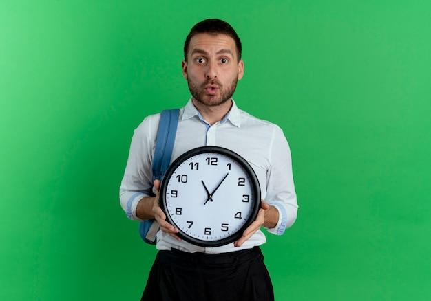 バックパックを身に着けている驚いたハンサムな男は、緑の壁に分離された時計を保持します
