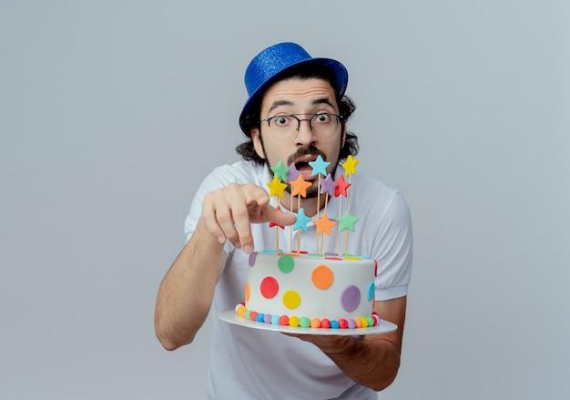 眼鏡と青い帽子をかぶってケーキを保持し、白で隔離のジェスチャーを見せて驚いたハンサムな男
