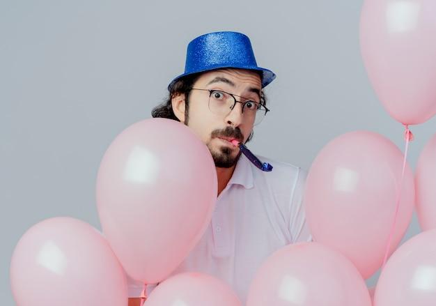 眼鏡と青い帽子をかぶって風船の後ろに立って、白で隔離の笛を吹いて驚いたハンサムな男