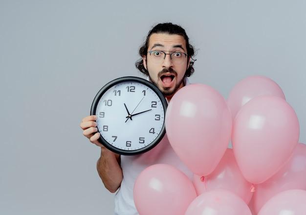 Uomo bello sorpreso con gli occhiali che tengono orologio da parete e palloncini isolati su bianco